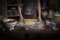 Woman rolling out dough with rolling pin — Stock Photo