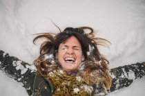 Woman lying on a snow bank — Stock Photo