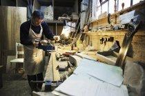 Человек, работающий в столярной мастерской — стоковое фото
