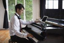Людина сидить на величному піаніно — стокове фото