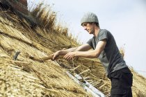 Young man thatching roof — Stock Photo