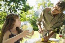 Mädchen und ein erwachsener Mann machen Limonade — Stockfoto