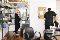 Cabeleireiro trabalhando no cabelo de um cliente — Fotografia de Stock