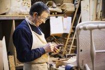 Человек, работающий на деревянном стуле — стоковое фото