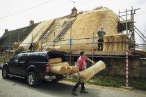 Тэтчер выгружает связки соломы — стоковое фото