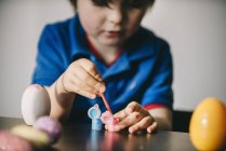 Boy painting eggs at Easter — Stock Photo