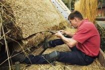 Thatcher trimming straw — Stock Photo