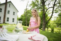 Girl cutting lemons, to make lemonade. — Stock Photo