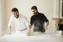 Bakers dusting bread dough with flour — Stock Photo