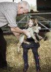 Agricultor e a menina com cordeiro recém-nascido — Fotografia de Stock
