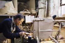 Homme travaillant sur une chaise en bois — Photo de stock