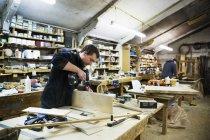Hombre de pie en un banco de trabajo - foto de stock