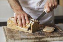 Panadero rebanando un pan recién horneado - foto de stock