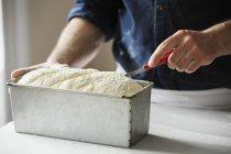 Baker cutting bread dough — Stock Photo