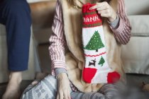 People unwrapping Christmas stocking presents — Stock Photo