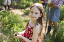 Menina segurando a planta com folhagem verde — Fotografia de Stock