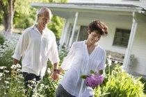 Mature couple walking through garden — Stock Photo