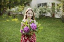 Girl holding bunch of flower heads — Stock Photo
