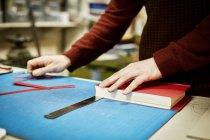 Человек восстанавливает книгу в мастерской — стоковое фото