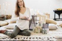 Жінка сидить на підставі, що тримає подарунок — стокове фото