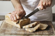 Baker slicing a freshly baked loaf — Stock Photo