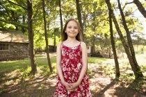 Girl standing in grove of trees — Stock Photo