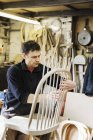 Man working on a wooden chair back. — Stock Photo