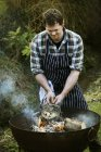 Chef grilling a fish on a barbecue. — Stock Photo
