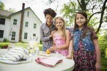 Женщина и двое детей, сделать лимонад — стоковое фото