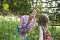 Mother and daughter in plant enclosure in garden — Stock Photo