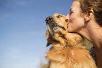 Mulher beijando um cachorro — Fotografia de Stock