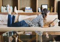 Mulher lendo um livro no sofá — Fotografia de Stock