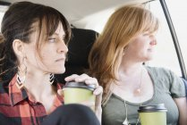 Women in a car with coffee cups. — Stock Photo