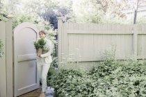 Woman entering a garden through a gate — Stock Photo