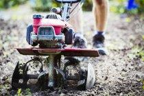 Homme utilisant rotivateur sur le sol — Photo de stock