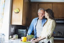Couple de personnes âgées souriant dans une cuisine — Photo de stock