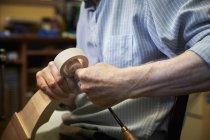 Создатель скрипки с помощью ручных инструментов — стоковое фото