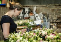 Florist working using digital tablet — Stock Photo