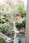 Femme portant un bouquet de fleurs blanches — Photo de stock