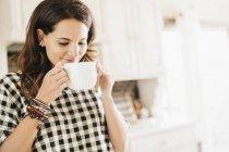Frau trinkt aus einem Becher — Stockfoto