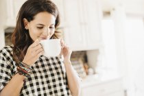 Woman drinking from a mug. — Stock Photo