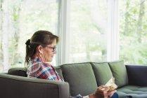 Mujer sentada en un sofá leyendo un libro . - foto de stock