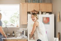 Blond woman standing at fridge — Stock Photo