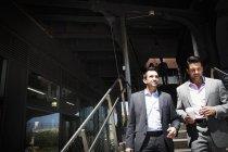 Businessmen walking down staircase — Stock Photo