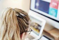 Donna ad una postazione di lavoro con due penne in capelli . — Foto stock