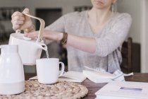 Woman pouring hot water into mug — Stock Photo