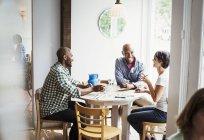 Homens e mulher almoçando no café — Fotografia de Stock