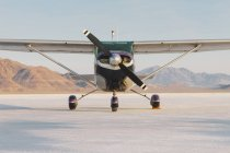 Small airplane parked on salt flats — Stock Photo