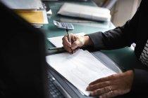 Бизнесмен, сидящий за столом в офисе — стоковое фото