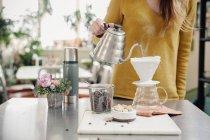 Woman pouring coffee — Stock Photo